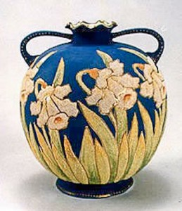 This delicate Coralene vase has a rich deep matte blue background which perfectly compliments the daffodils which encircle the entire vase. 1909 back stamp.
