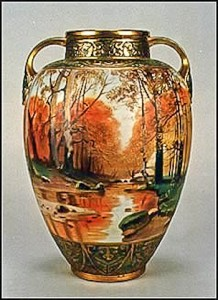 This large scenic vase represents to many what is classical Nippon. A rich landscape scene in earthtone colors is complimented by beautifully detailed trim at the top and bottom. This vase has the green M-in-wreath backstamp.
