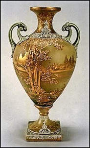 This stunning bolted urn features a scene of raised trees with applied gold decoration. In addition, clay moriage trim highlights the handles, upper and lower portions of this urn. Gold lustre is utilized for the scene which encircles this beautiful piece. The back stamp is the green M-in-wreath.