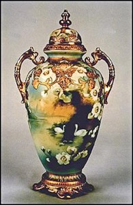 This is a covered urn decorated with a beautiful scene of swans on a peaceful lake. Dogwood blossoms surround the scene. Swans were the subject matter for many different scenes during the Nippon era, and this is one of the most lovely. The backstamp on this vase is the blue maple leaf.