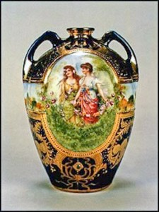 This gorgeous cobalt blue vase features a decal portrait of two Victorian ladies in a garden. The scenic panel encircles the entire vase. Elaborate gold trim highlights this exquisite vase. The backstamp on this vase is the blue maple leaf.