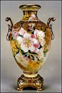 This bolted urn features beautifully painted lillies on the front & back. Extensive gilding adds richness to this exquisite example of Nippon from the Victorian era. The back stamp is the blue Maple Leaf.