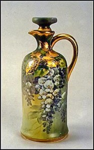 This wine claret would certainly have been the envy of the neighborhood when it was new in about 1911. Lush wisteria flows down the front and is complimented by the extensive use of gold decoration. The backstamp on this vase is the blue maple leaf.